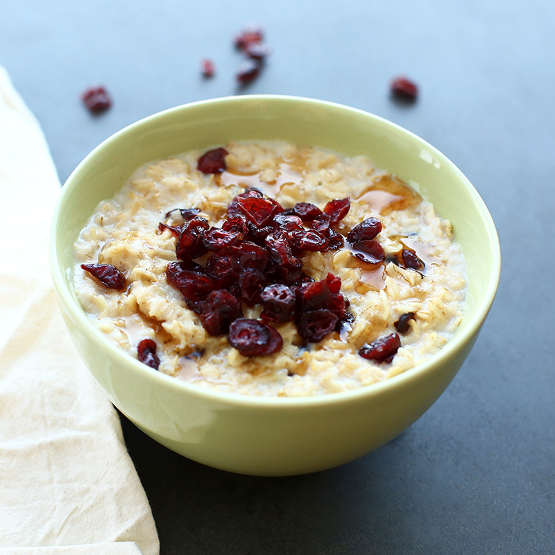 a bowl of Quaker oats porridge with cranberries and maple syrup on top
