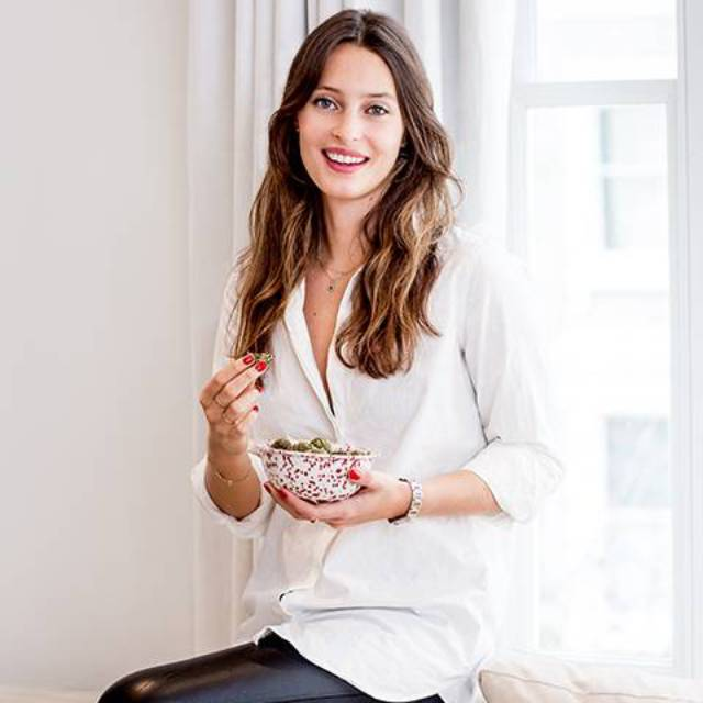 Ella Woodward eating her Deliciously Ella's chocolate and hazelnut overnight oats, sitting on the side of a sofa