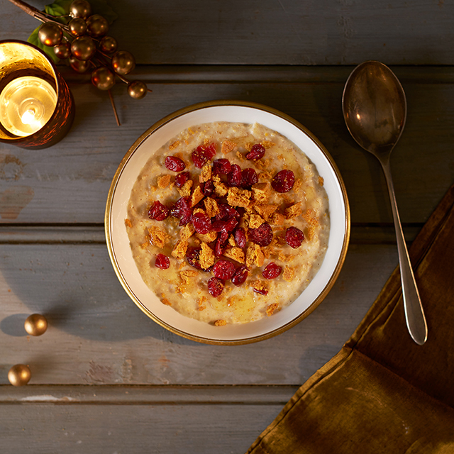 bowl full of gingerbread porridge topped with cranberries, crushed biscuits and honey