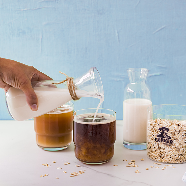 Oat milk being poured into a cup of tea