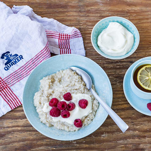 a bowl of Quaker oats porridge topped with raspberries and low-fat yogurt drizzled over the top
