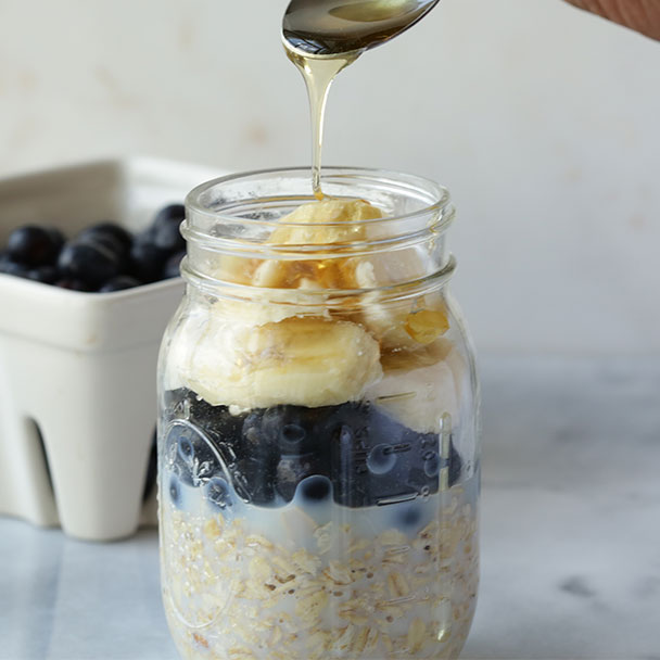 blueberry banana overnight oats topped with a drizzle of honey