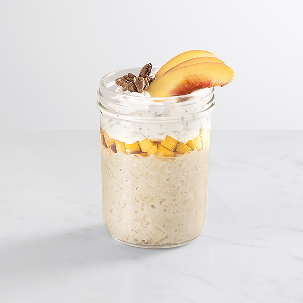 chia peach overnight oats topped with pecans and peach slices in a glass