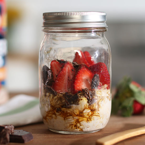 chocolate strawberry overnight oats layered with strawberries, honey and chocolate shavings