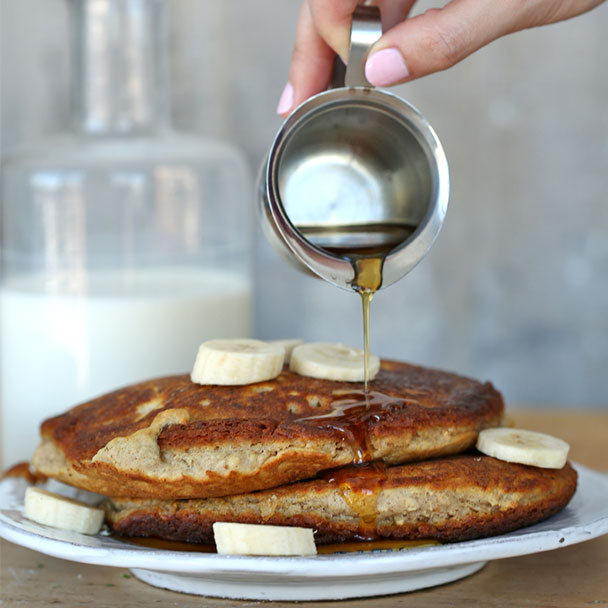 hearty banana oat pancakes served with warm syrup on a plate